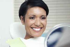 Smiling woman in dental chair looking at smile in mirror