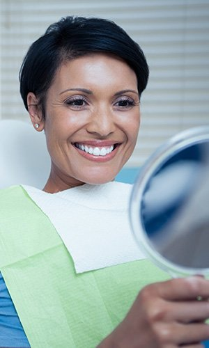 Woman in dental chair looking at smile in mirror