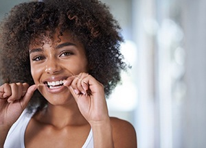 young woman smiling while flossing