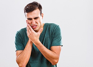 man holding his mouth in pain
