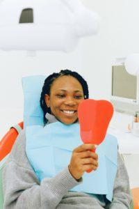 Woman holding dental mirror at dentist